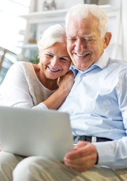 An older couple seated on a couch using a laptop to converse with family and smiling after receiving full-mouth reconstruction in Marble Falls