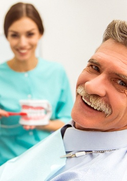 An older man smiling while a dental hygienist explains how to maintain his new and improved smile
