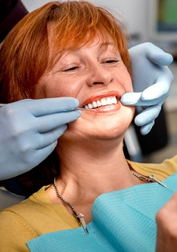 An older woman with red hair looking at her smile in the mirror as a dentist explains what work needs to be done