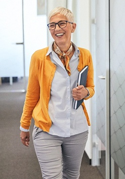 An older woman wearing business casual clothing and smiling as she walks down the hallway of her office