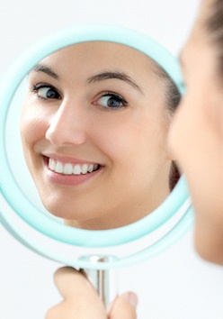 A young female looking at her new appearance in the mirror after undergoing a smile makeover