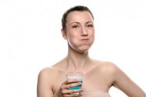 woman using mouthwash thanks to recommendations from the dentist marble falls trusts