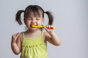 Smiling little girl in pigtails brushing her teeth happily