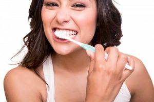 young attractive woman smiling while brushing her teeth