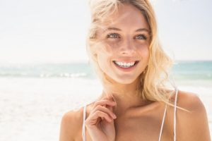 A woman smiling outside on the beach.